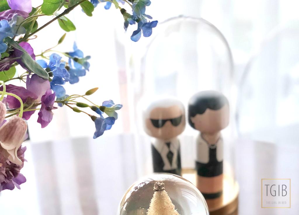 Poppen van Karl Lagerfeld en Coco Chanel onder een stolp