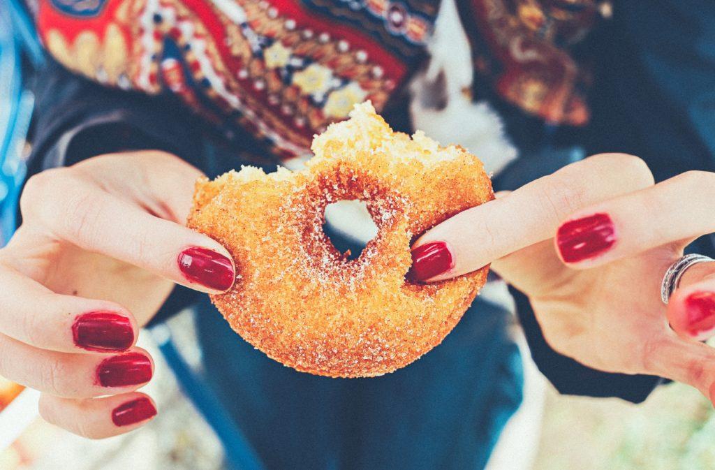 Vrouw met rode nagels houdt donut vast