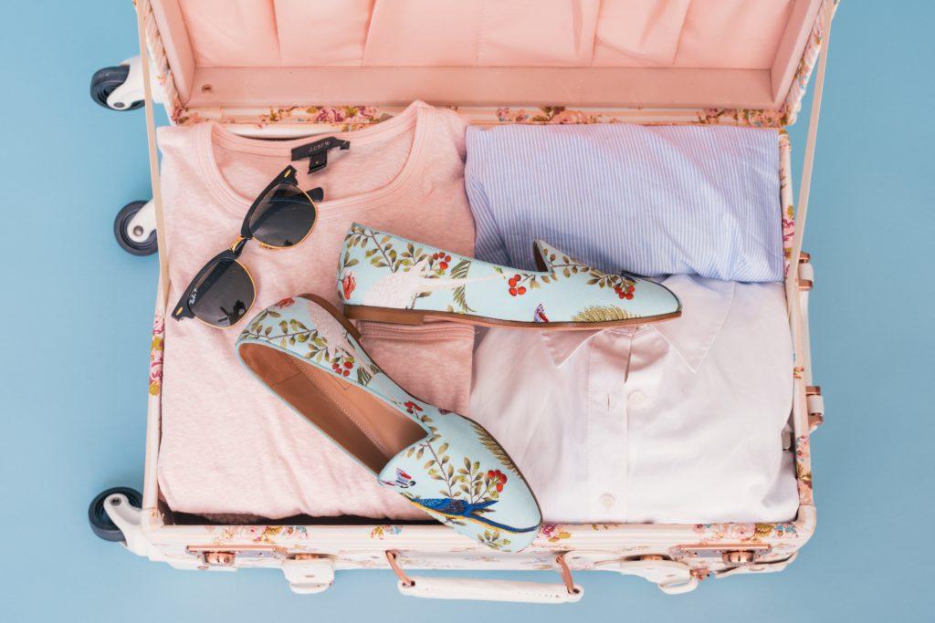roze koffer gevuld met kleding, zonnebril en bloemetjes schoenen