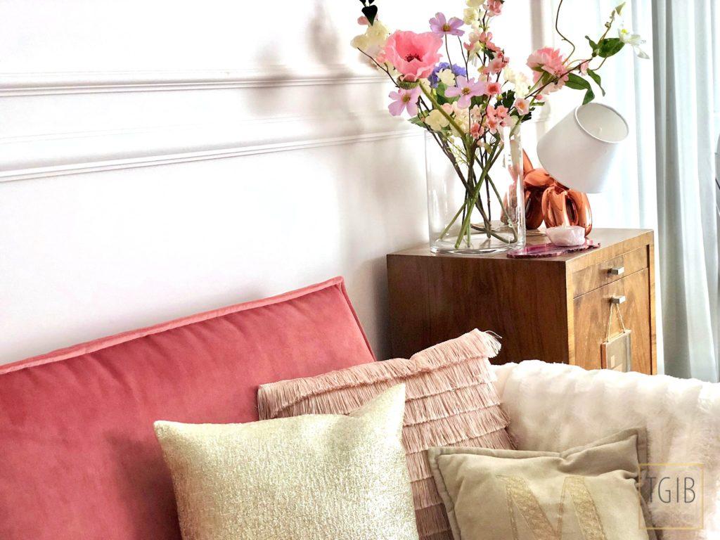 roze bank met kussens en bloemen in woonkamer