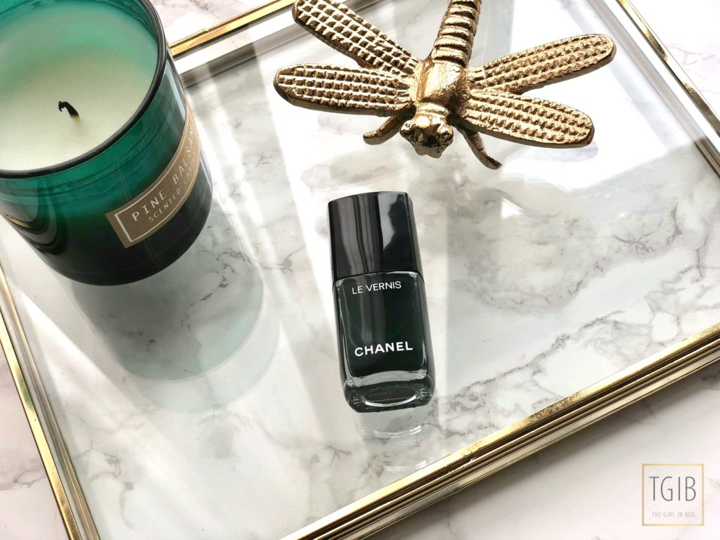 Chanel nail polish with ornament and a green candle