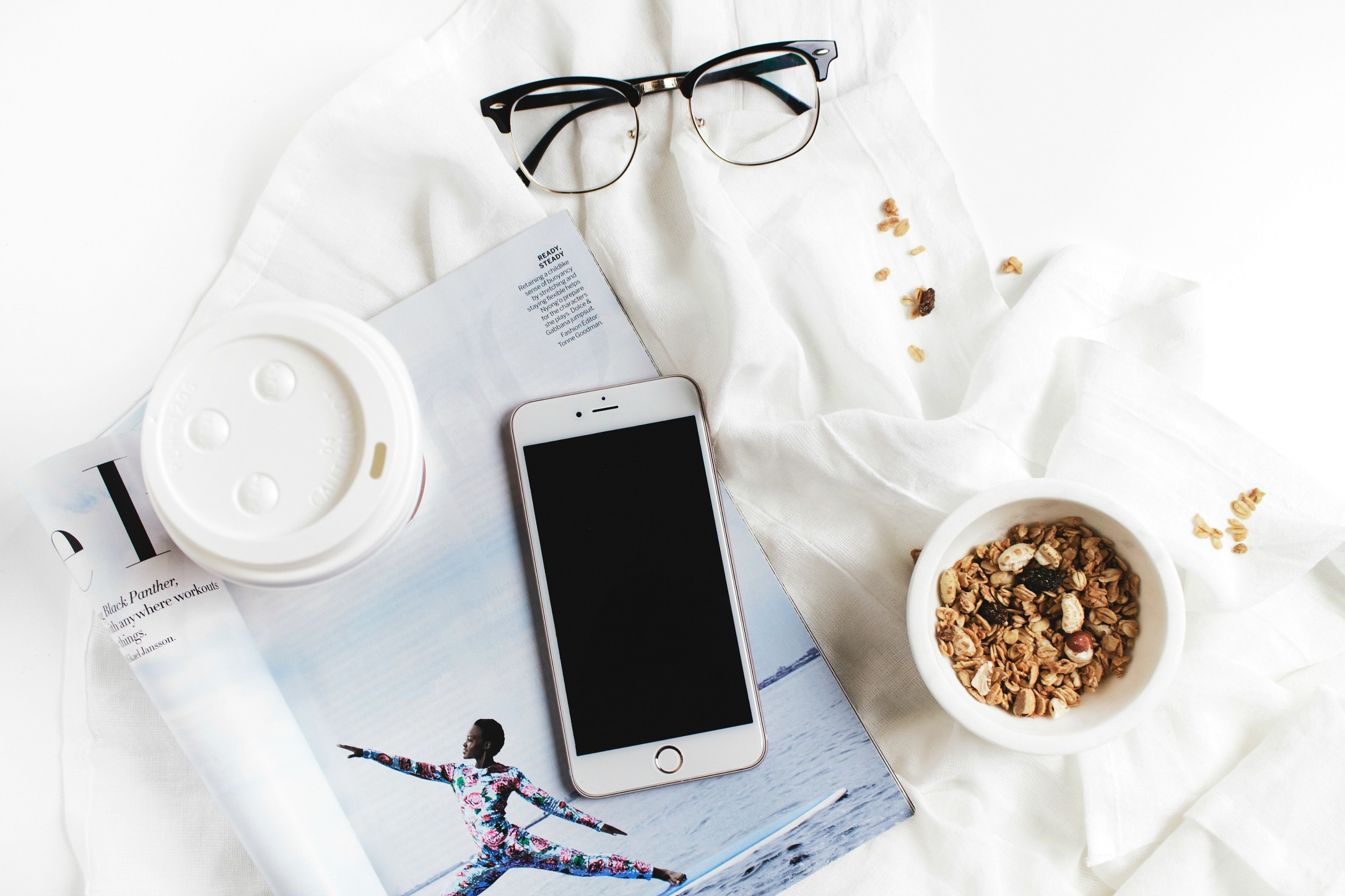 white flatlay with iPhone and granola